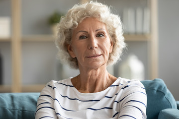 Head shot portrait close up beautiful aged mature woman with grey curly hair sitting on cozy couch, posing for photo at home, attractive older senior female looking at camera, natural old beauty Fotomurales