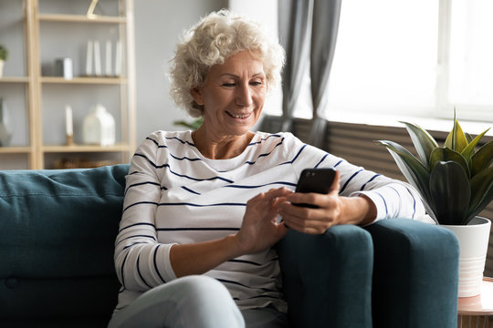 Happy smiling older woman using phone, looking at screen, sitting on cozy sofa in living room, excited mature senior female chatting in social network or shopping online, having fun with smartphone