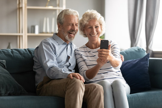Excited mature couple having fun with phone together, posing for photo, taking selfie, smiling older woman holding smartphone, looking at screen, watching funny video, sitting on cozy couch