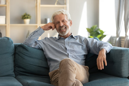 Portrait smiling mature man sitting on couch alone in modern living room at home, happy excited older male with healthy toothy smile looking at camera, posing for photo on cozy sofa