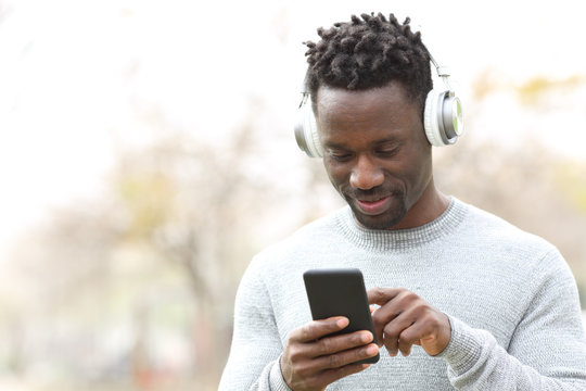 Happy black man listening music on phone with headphones