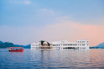 Fotomurales - Romantic luxury India travel tourism - tourist boat in front of Lake Palace (Jag Niwas) complex on Lake Pichola on sunset with dramatic sky, Udaipur, Rajasthan, India