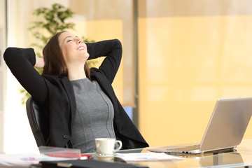 Happy executive woman breathing fresh air at her desk