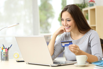 Happy woman paying with credit card on laptop