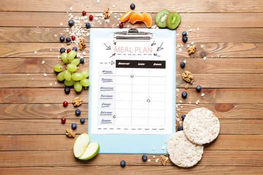 Healthy products and meal plan on wooden background