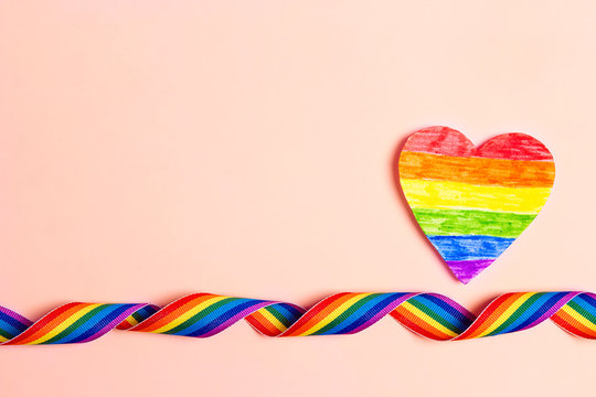 LGBT rainbow ribbon and paper rainbow heart on a pink background.