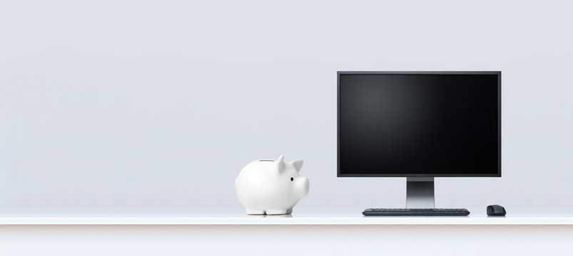 Clean white office desk with piggy bank and desktop computer.