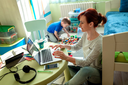 Mother working remotely on laptop while taking care of her son playing with toys in his room.