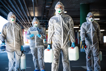 Team of healthcare workers wearing hazmat suits working together to control an outbreak