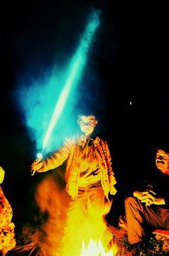 Portrait Of Confident Boy Holding Lightsaber By Bonfire At Night