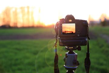 Aparat fotograficzny z krajobrazem zachodzącego słońca na obszarze wiejskim.