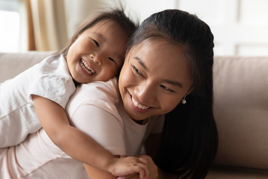 Little daughter piggybacks her Asian mother family play on couch in living room, close up. Excited mom laughing enjoy funny time together with preschool kid at home, have fun, happy motherhood concept