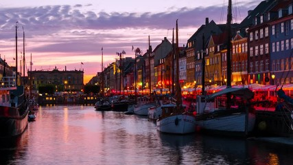 Wall Mural - Copenhagen, Denmark. Time-lapse at sunset. View of famous Nyhavn area in the center of Copenhagen, Denmark. Various boats moored with historical buildings and cloudy sunset bright sky