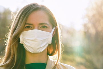 Young woman wearing white cotton virus mouth nose mask, nice backlight sun bokeh in background, closeup face portrait Wall mural