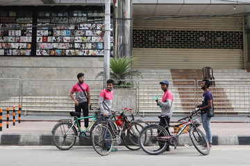 Online food delivery men with their bicycles wait in front of a restaurant to receive orders amid concerns over the coronavirus disease (COVID-19) outbreak in Dhaka