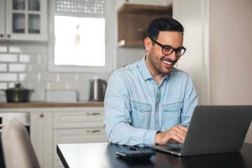 Businessman working on laptop at home.