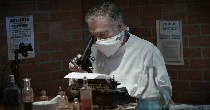 Medical scientist from 1918 in a small laboratory during the Spanish Flu influenza pandemic with a typwriter near by to document his findings.