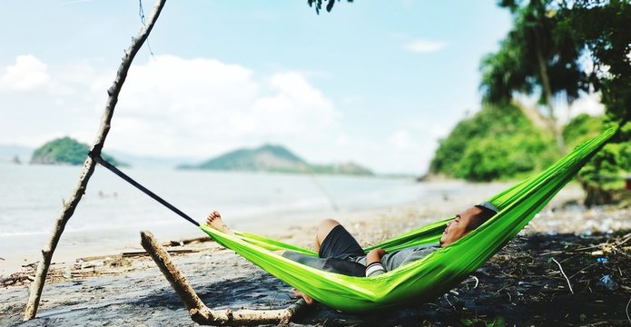 Man Relaxing On Hammock At Beach