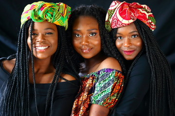 african models wearing traditional headdress posing for the camera