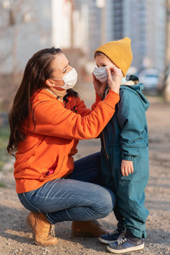 A mother helps put on a medical mask for her child outdoors during the coronavirus pandemic and Covid -19.