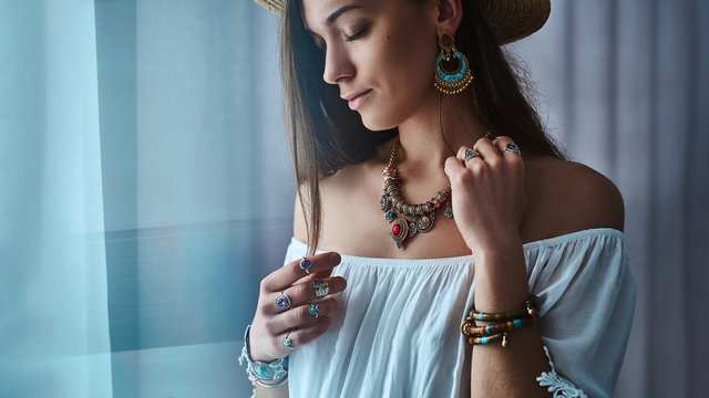 Stylish brunette boho chic woman wears white blouse and straw hat with big earrings, bracelets, golden necklace and silver rings. Fashionable hippie gypsy bohemian outfit with jewelry details