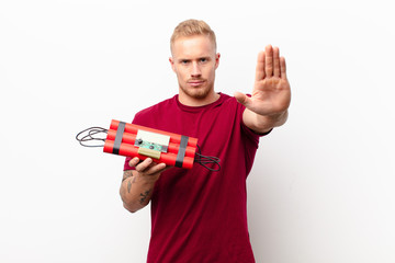 young blonde man looking serious, stern, displeased and angry showing open palm making stop gesture against white wall holding a dynamite explosive