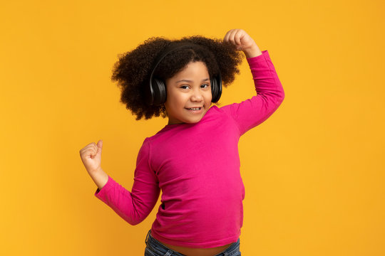 Positive funny african american girl wearing wireless headphones and dancing