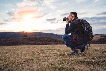 Photographer shoots a sunset in the mountains. Fotobehang