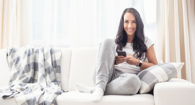 Beautiful brunette woman sitting on a white sofa next to grey and white blanket and pillow, smiling to the camera, holding a phone