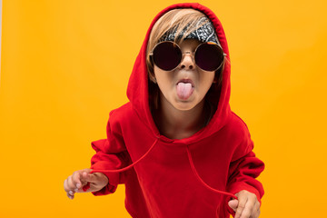 Cool young boy in red hoody and white t-shirt, picture isolated on orange background