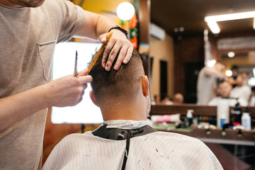 Cropped view of hairdresser doing hairstyle and style with scissors and comb. Concept Barbershop.