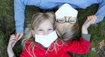 girl and boy lie on the grass in a facial mask during the coronavirus pandemic