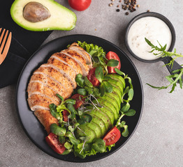 Fototapete - roasted sliced chicken fillet with avocado, tomatoes and herbs on a plate healthy nutrition
