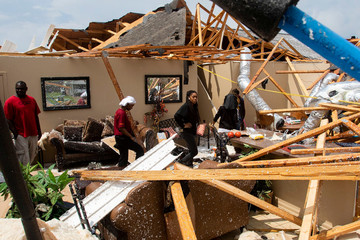 Residents comb through the wreckage of a collapsed house after an Easter Sunday tornado in Monroe