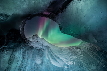 Wall Mural - Northern lights aurora borealis over glacier ice caves in Iceland