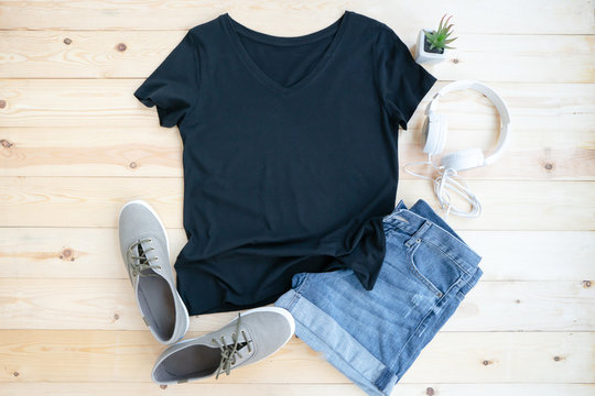 Black female t shirt mock up flat lay on wooden background. Top front view
