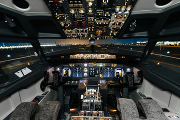 Full view of cockpit modern Boeing aircraft before take-off. Airplane is ready to fly. Night shot in cabin. Safety flight