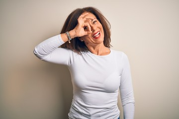 Wall Mural - Middle age beautiful woman wearing casual t-shirt standing over isolated white background doing ok gesture with hand smiling, eye looking through fingers with happy face.