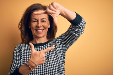Wall Mural - Middle age beautiful woman wearing casual sweater over isolated yellow background smiling making frame with hands and fingers with happy face. Creativity and photography concept.