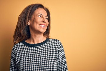 Wall Mural - Middle age beautiful woman wearing casual sweater over isolated yellow background looking away to side with smile on face, natural expression. Laughing confident.