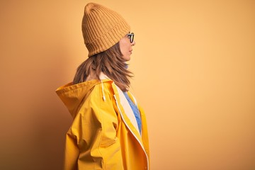 Wall Mural - Middle age woman wearing yellow raincoat and winter hat over isolated background looking to side, relax profile pose with natural face with confident smile.