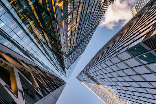 Looking up a reflections on glass covered corporate building