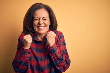 Wall Mural - Middle age beautiful woman wearing casual shirt standing over isolated yellow background excited for success with arms raised and eyes closed celebrating victory smiling. Winner concept.