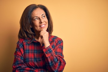 Wall Mural - Middle age beautiful woman wearing casual shirt standing over isolated yellow background with hand on chin thinking about question, pensive expression. Smiling and thoughtful face. Doubt concept.
