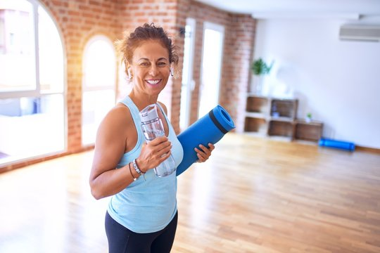 Middle age beautiful sportwoman smiling happy and confident. Standing with smile on face holding mat and bottle of water before doing exercise at gym
