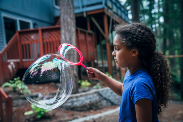 Girl blowing giant bubbles in the back yard of house