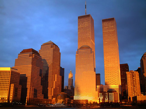 Illuminated World Trade Center And Buildings Against Blue Sky At Dusk