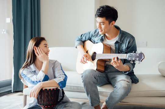 Asian young lovers play and sing at home