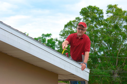 Wind mitigation inspection inspector on a ladder doing inspection on new roof to create a report and risk rating for homeowner to send to their insurance company to receive deductions in policy costs.