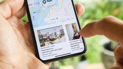 NEW YORK CITY, NY  December 1, 2019: Woman trying to book home apartment room in New York City using Airbnb app